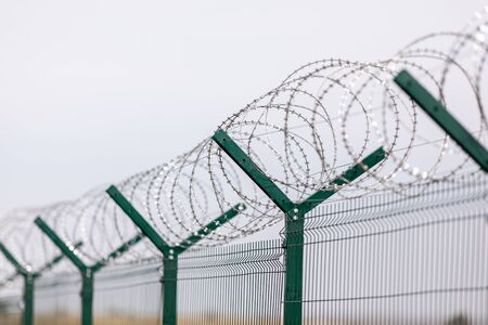 Fencing of sensitive sites with barbed wire. Barbed wire. Restriction of freedom. Prison fence. Forbidden territory. The concept of security. The concept of the ban Stock fotó