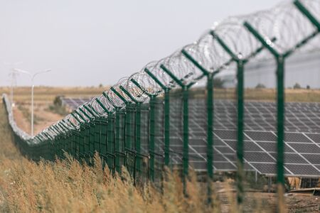 Solar power station protected from road by barbed wire fence. Fencing of sensitive sites with barbed wire
