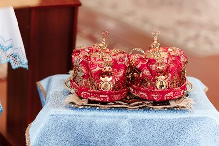 Golden crowns and cross laying on a church table ready for a wedding ceremony. Wedding crowns. Wedding crown in church ready for marriage ceremony. 版權商用圖片