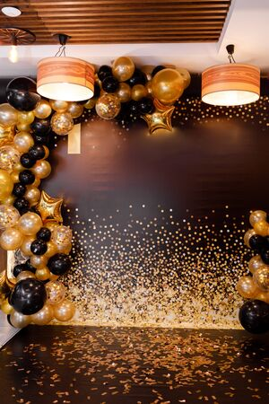 golden and black balloons. The photo zone is decorated with black and yellow balloon. stylish party with balloons. place of celebration.