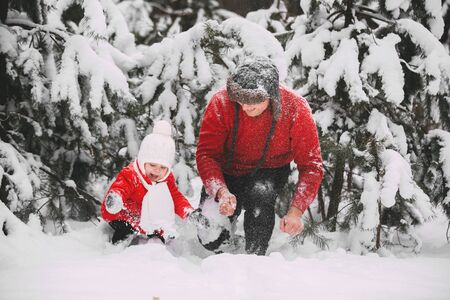 Portrait of happy little girl in red coat with dad having fun with snow in winter forest. girl playing with dad