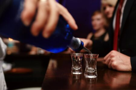 Bartender pouring strong alcoholic drink into small glasses on bar, shots in a nightclub or bar. 版權商用圖片
