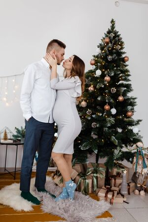 Christmas family photo with christmas tree and ornaments, wooden floor and fireplace. Man and woman are kissing near christmas tree. Stock Photo