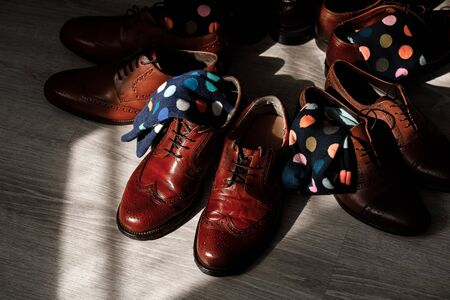 stylish mens socks. Stylish suitcase, mens legs, multicolored socks and new shoes. Concept of style, fashion, beauty and vacation.