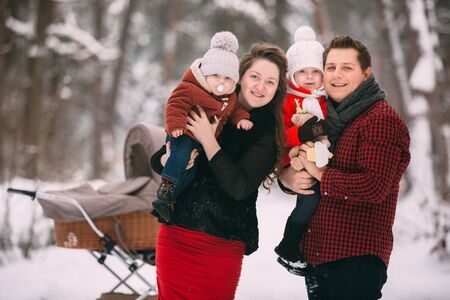 A beautiful family enjoying in the winter snowy forest. Mother, father, daughter and baby son enjoying day outdoors. Holidays, christmas, happiness together, childhood in love. Stock fotó