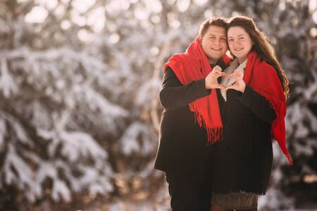 Valentine's Day. loving young couple having a good time in winter snowy forest. Hands folded in heart. concept of family and love Stock Photo - 135664726