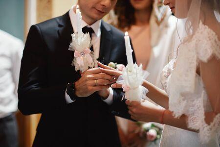 De hand van de bruid draagt een gouden verlovingsring aan de vinger van de bruidegom. Trouwdag. Handen met trouwringen. Detailopname.