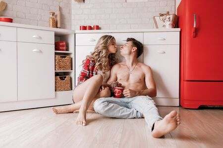 Lovely girl sitting on the floor and having fun with boyfriend. Young couple enjoying coffee or tea in the kitchen. happy valentine's day Stock Photo - 137389863