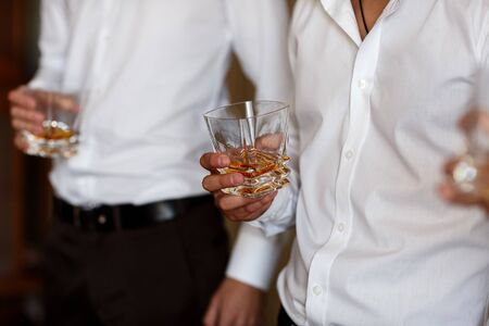 stylish friends businessmen in suits toasting with glasses of whiskey indoors, closeup. groom's morning.