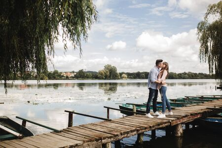 Young romantic couple is having fun in summer sunny day near the lake. Enjoying spending time together in holiday. Man and woman are hugging and kissing Foto de archivo - 138047582