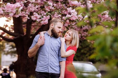 Stylish couple near the Sakura tree with blooming pink flowers. beautiful young couple, man with beard and blonde woman hugging in the spring park. Concept spring. fashion and beauty.