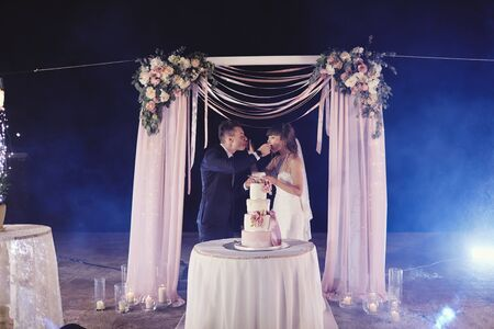 gorgeous bride and stylish groom tasting their stylish wedding cake. happy newlywed couple eating piece of cake, funny emotional moment Reklamní fotografie