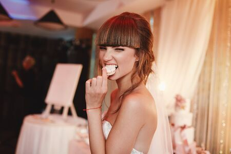 portrait of stylish cheerful bride eating french macaroon dessert. wedding and holiday concept. Banque d'images - 138299758