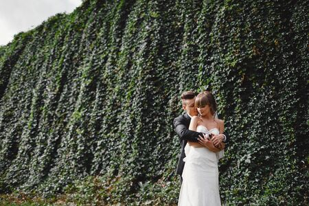Happy young bride and groom on their wedding day. groom and bride hugging in front wall with green ivy. Foto de archivo - 138299800