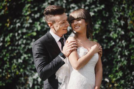 Geweldig lachend bruidspaar. Mooie bruid en stijlvolle bruidegom. bruidegom en bruid poseren voor de muur met groene klimop. Stockfoto