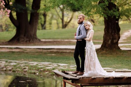 young man with beard and bride in luxury long dress hugging near lake in park with blooming cherry or sakura blossoms on background. Wedding spring day.