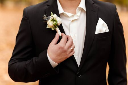 white roses flowers in buttonhole, the groom is dressed in a dark suit and a white shirt. Wedding ceremony, elegant suit. Outfit of the day