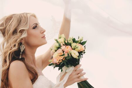 portrait of a beautiful blonde bride with a bouquet of flowers ith wedding makeup and hairstyle. luxury bride with veil over her face. Closeup portrait of young gorgeous bride. Wedding. copy space. 免版税图像 - 140279691