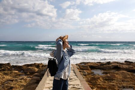 female traveler admiring a marine view. tourism in Cyprus. tourist on sea background. girl travels on the beaches. young beautiful hipster woman on tropical beach, summer vacation, happy, fun