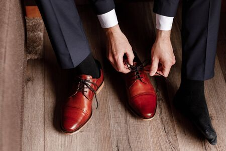 groom tied the laces on the shoes close up. business man is hanging shoes indoor in hotel room. mans hands and pair of leather mens shoes. meeting of the bridegroom. business mans morning.