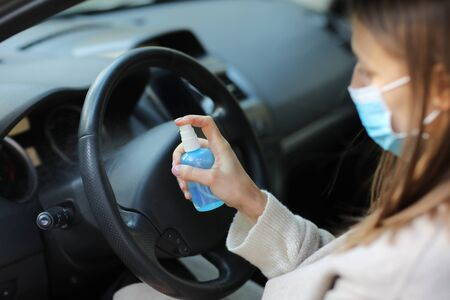 Spraying anti-bacterial sanitizer spray on hand in car, infection control concept. Sanitizer to prevent Coronavirus, Covid-19, flu. Spray bottle. womanwearing in medical protective mask driving a car