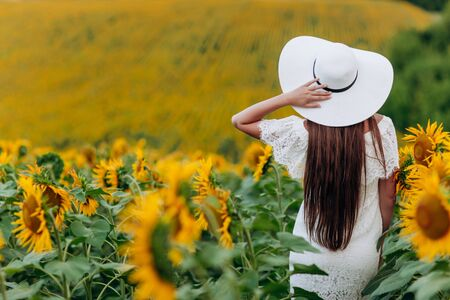 Woman in the field of sunflowers. A happy, beautiful young girl in a white hat is standing in a large field of sunflowers. Summer time. Back view