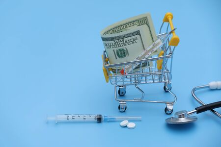 yellow shopping cart with pills stands on dollar bills on a blue background close-up. Concept of healthcare, online shopping, high cost of medicines. expensive medicine. selective focus. 스톡 콘텐츠