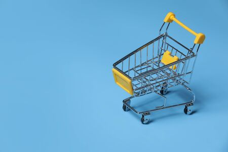 close-up of shopping trolley on blue background with some copy space. empty shopping cart on blue background.