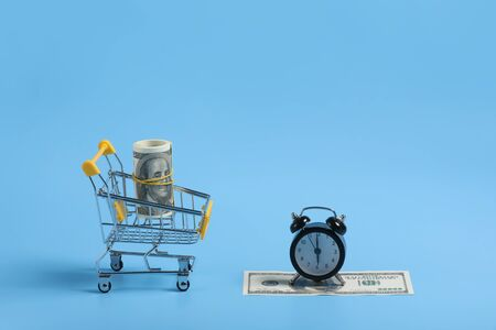 shopping time. Alarm clock and dolar on blue background. time is money. Time management concept. money in the basket. selective focus. place for text.