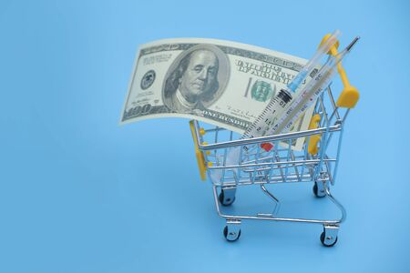 Dollar bills roll and thermometer in shopping cart on shopping. Medicine concept with copy space