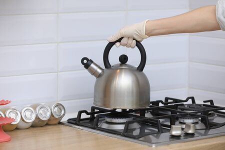 woman puts a kettle on the kitchen in gloves on gas stove. Stovetop whistling kettle in hand. selective focus.