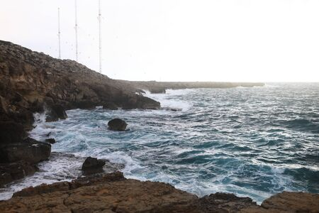 Waves hitting the rocky cliffs in a beach located in Cyprus,This weather might be dangerous for water sports but simultaneously the waves and their splashes are pretty and wild.