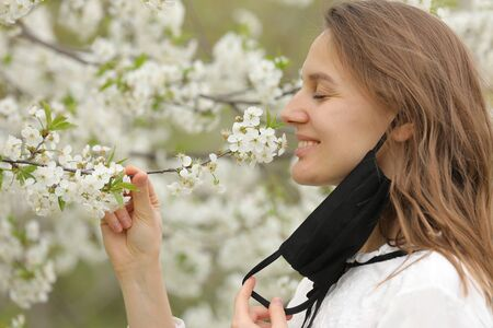 happy beautiful girl took off her medical mask to breathe in the smell of flowers. A girl in a mask stands in blossoms. the end of quarantine.