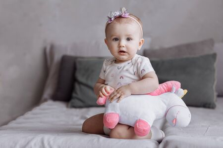 adorable little girl is playing with toy unicorn on bed at home. concept of childhood day. happy baby's, family day.