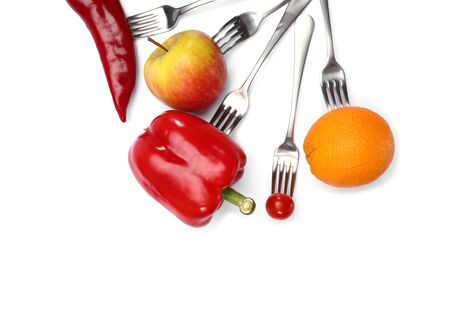 A healthy diet food. fresh cherry tomato, red pepper, cucumber, apple and orange fruits on forks on white background. Healthy eating and vegetarian food, cooking concept Фото со стока