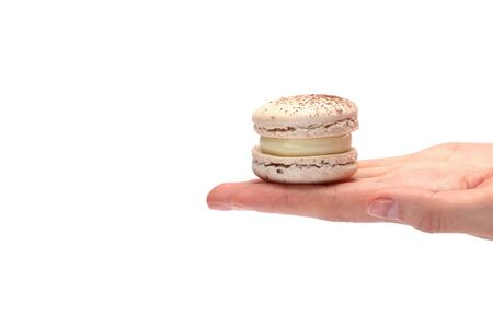 Tasty colorful chocolate macaroon or macaron in female hand isolated on white background. 스톡 콘텐츠 - 146375053