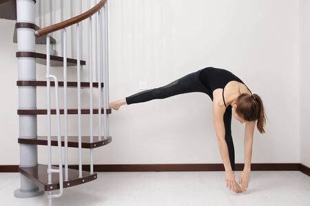 Does exercises. Young woman with slim body shape in sportswear have fitness day indoors at home. stay at home concept Фото со стока