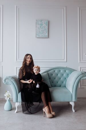 Happy young mom on stylish couch relax with little daughter in black dresses and posing, smiling mother and girl child have fun at studio. family look.