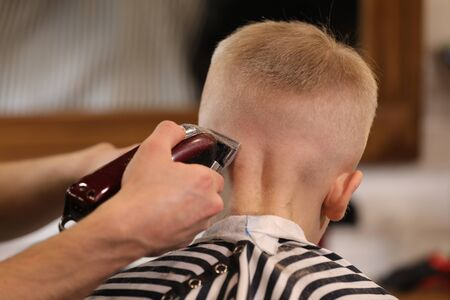 Mens hairstyling, haircutting, in a barber shop or hair salon. Close-up of man hands grooming kid boy hair in barber shop. Boy cut with hairdressers machine.
