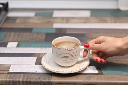 Female hands hold a coffee mug or cup on a colorful table. copy space. selective focus.
