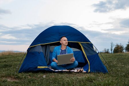 male freelancer is working on a laptop outdoors in mountains. Freelance concept.