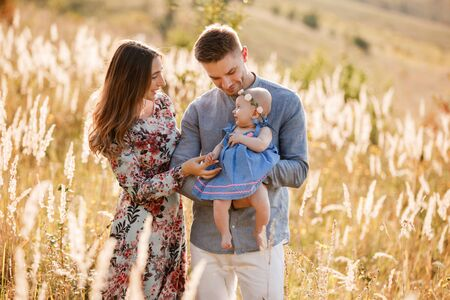 mom, dad and little girl having fun outdoors in the grass on summer day. mothers, fathers and babys day. Happy family for a walk.