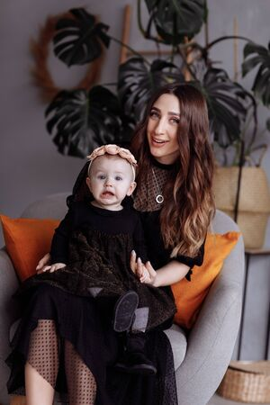 Beautiful mother sits on a chair and keeps her daughter on lap at home. family look concept. mothers, babys day.