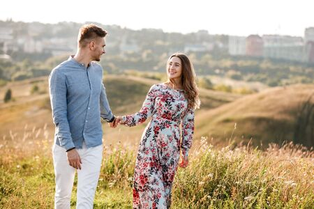 Young couple is hugging and walking in summer field with grass on the background town. Man and woman. Concept of lovely family.
