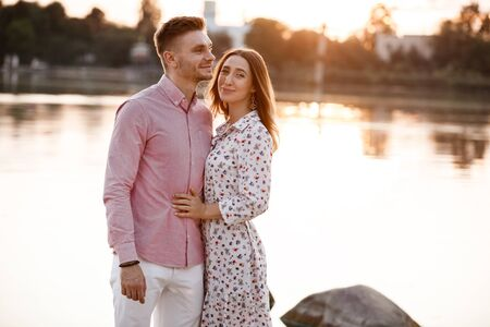 Young couple is hugging and walking at sunset near the lake. Man and woman on summer holiday. Concept of lovely family.