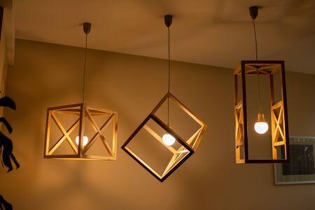 Modern ceiling lights bulbs lamp made of wooden frame geometric shape interior and loft style decorating with white wooden wall.