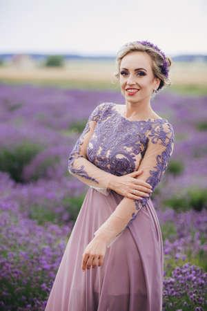 Portrait of beautiful romantic woman in purple dress in field of lavender