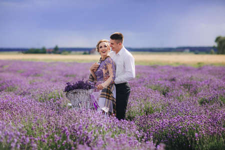 Happy young couple are walking with retro bicycle in lavender field. woman in purple dress and with hairstyle is hugging her man outdoors.