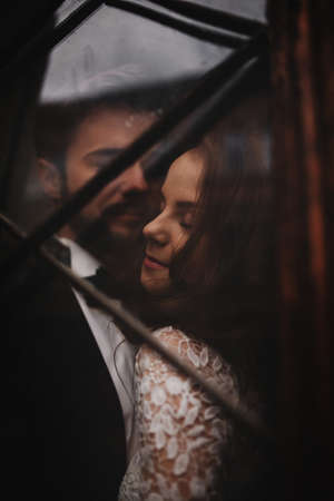 Young stylish newlyweds are hugging behind old rustic wooden door. wedding day
