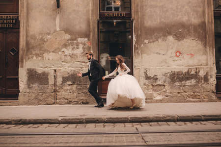 Happy newlyweds couple on a walk in old European town street, gorgeous bride in white wedding dress together with handsome groom